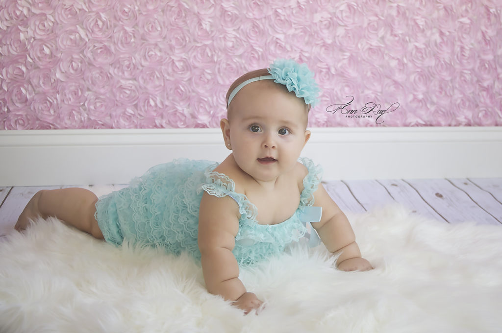 Child Photographer in St. Louis Baby wearing an aqua romper with pink floral backdrop