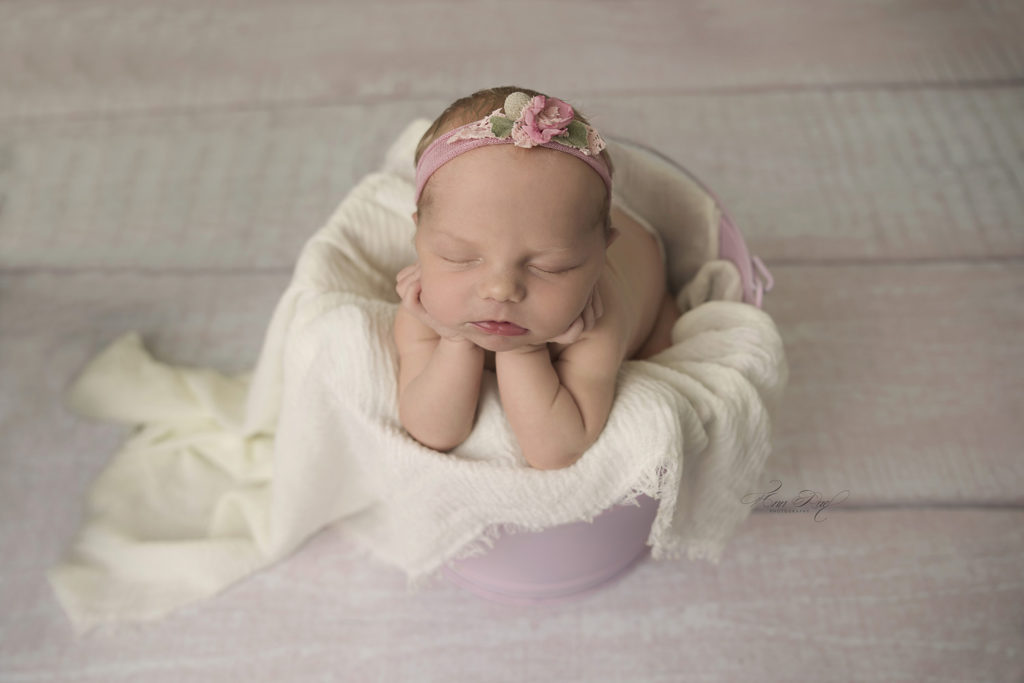 Bbay girl in a pink bucket posed newborn session
