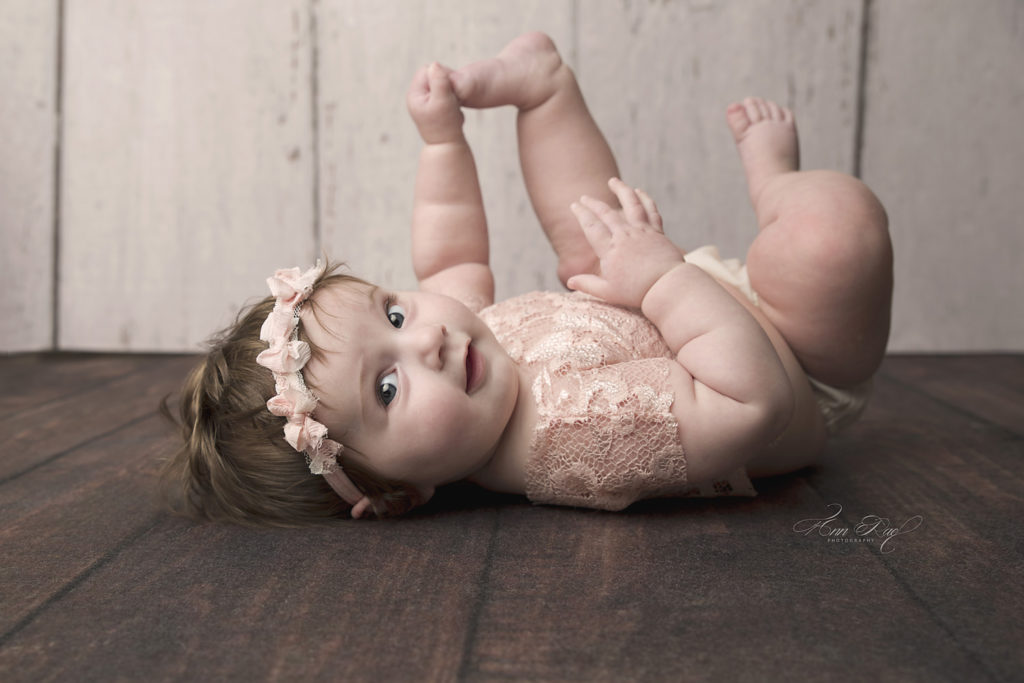 Baby grabs her toes during her tummy time session in St. Louis