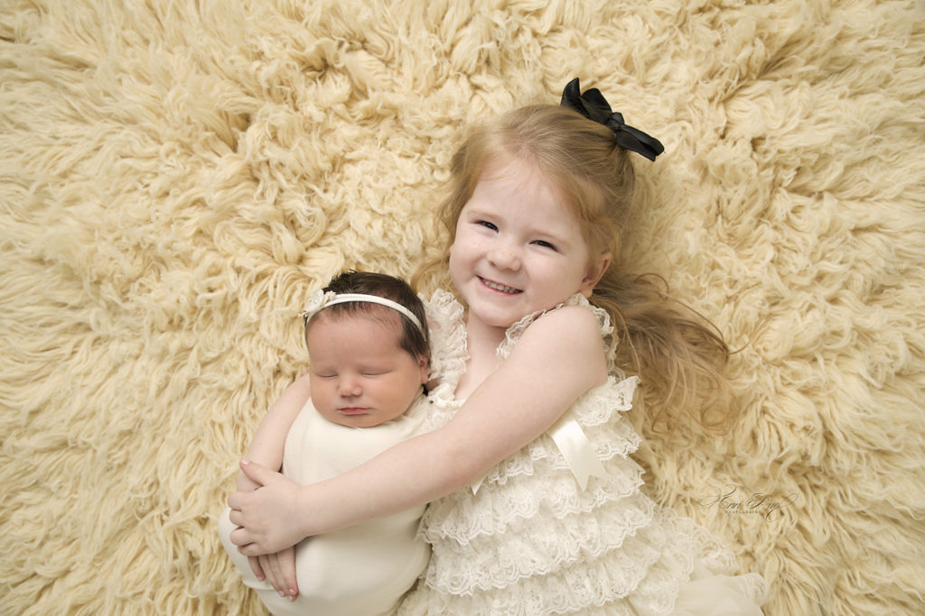 Big sister posed with her newborn sibling in STL