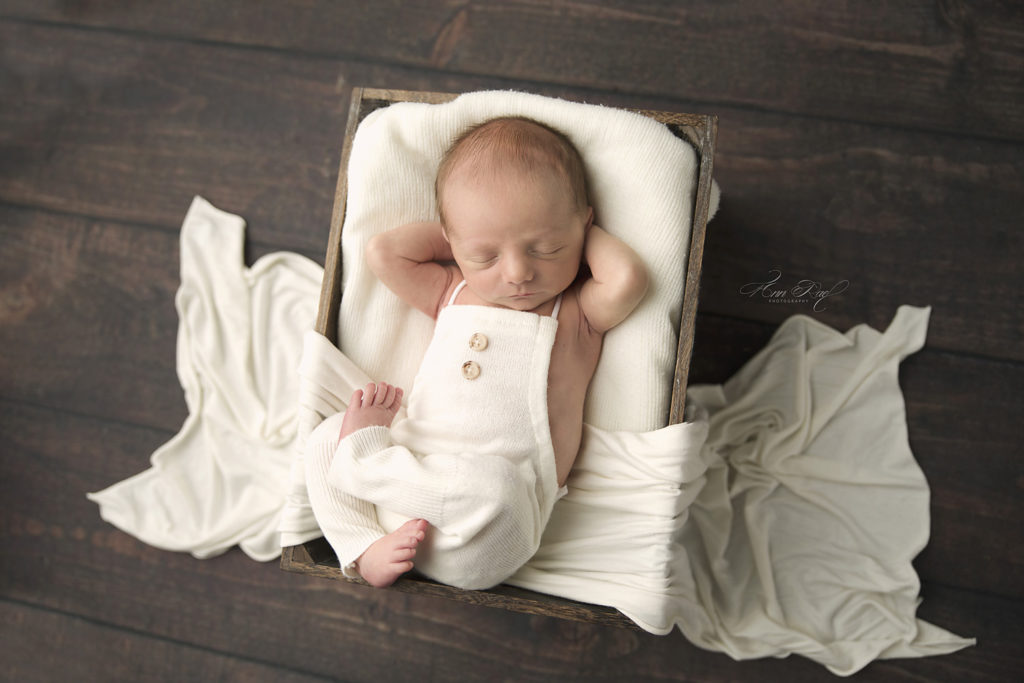 Baby boy relaxing in a basket for photography session