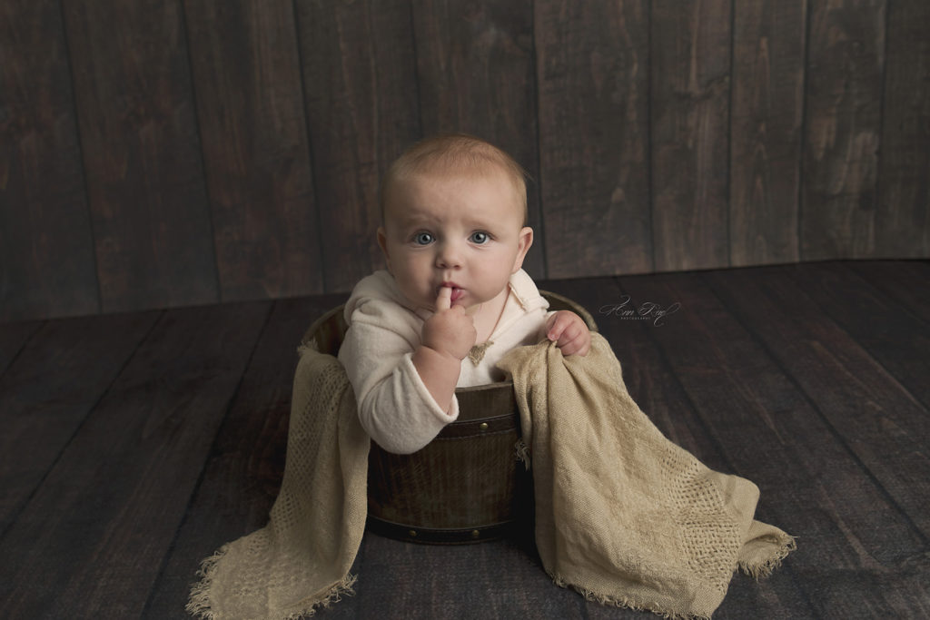 Baby boy posed in a bucket by St. Louis Child Photographer