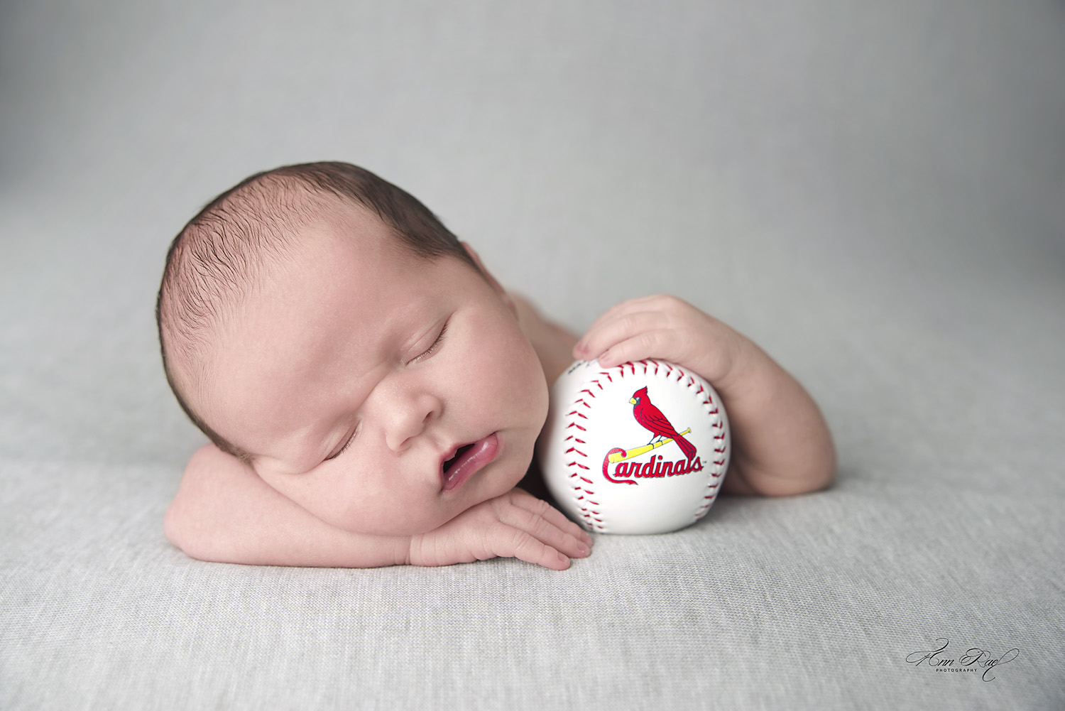 St. Louis Newborn Photographer with Cardinals baseball for portfolio