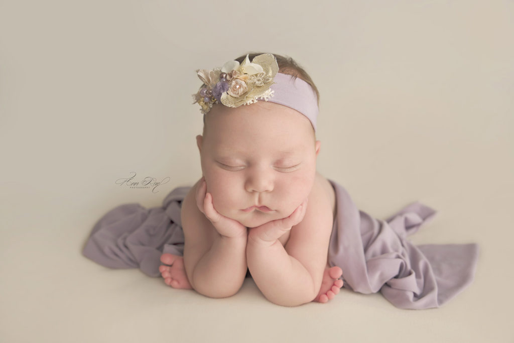 Newborn Session Baby Picture Posed wearing lavender wrap and headband