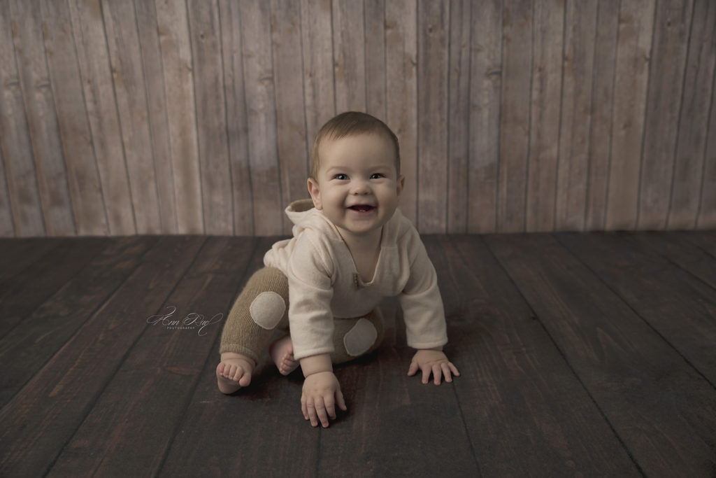 St. Louis Baby Having His Portraits taken on a wood backdrop